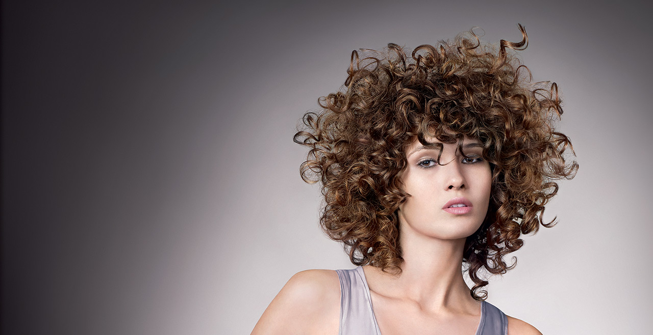 Female model with curly hair against a grey background